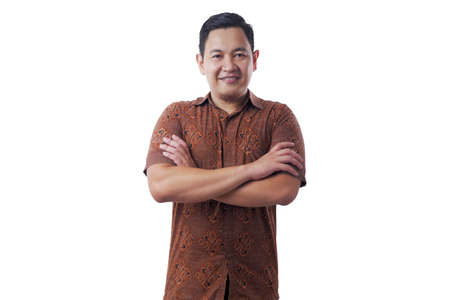 Portrait of happy successful Asian man wearing batik shirt smiling confidently wit arms crossed on his chest, isolated on white Banque d'images