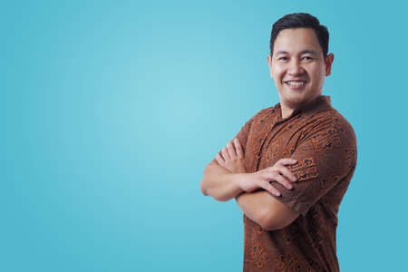 Portrait of happy successful Asian man wearing batik shirt smiling confidently wit arms crossed on his chest, against blue background Stock Photo