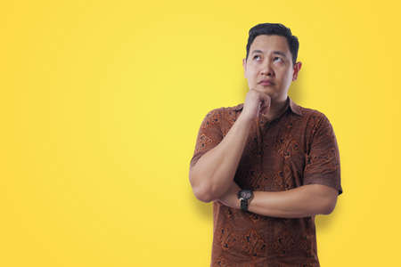 Portrait of young confused Asian man wearing batik shirt shows thinking expression, looking up contemplation gesture over yellow background