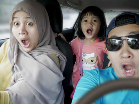 Portrait of Asian muslim family in mudik trip, shocked gesture about to have car accident