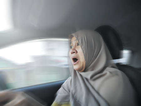 Portrait of female Asian muslim driver shocked and panic about to have crash accident, zoomed motion blur defocus concept Imagens