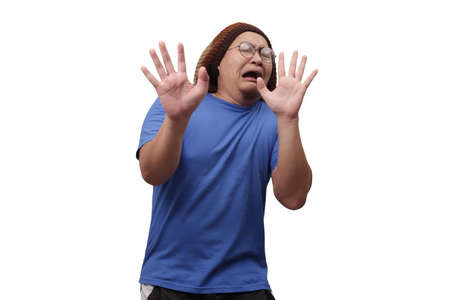 Portrait of funny young Asian man afraid expression with hands raised up, surrender gesture, isolated on white