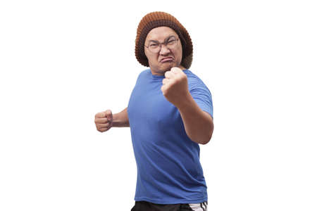 Portrait of funny Asian man showing cynical unhappy angry facial expression putting up his fist challenge to fight