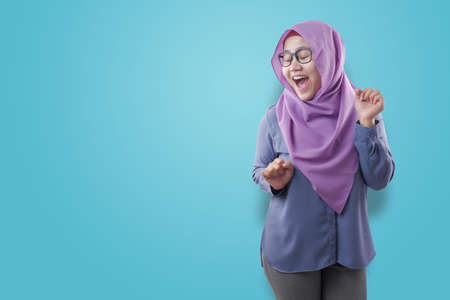Portrait of a funny young Asian muslim woman wearing hijab dancing happily joyful expressing celebrating good news victory winning success gesture, smiling positive excited emotion isolated on white
