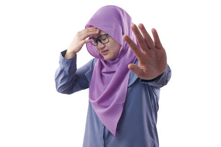 Portrait of sad Asian muslim woman having bad experience making stop hand sign gesture, bullied concept 写真素材