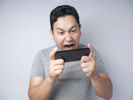 Imagen fotográfica retrato de un lindo joven asiático guapo con cara divertida jugando juegos en tableta, expresión triste perder enojado