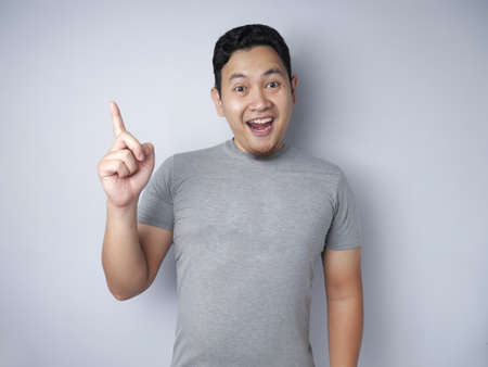 Portrait of young Asian man looked happy, thinking and looking up, having good idea. Half body portrait against grey wall with copy space
