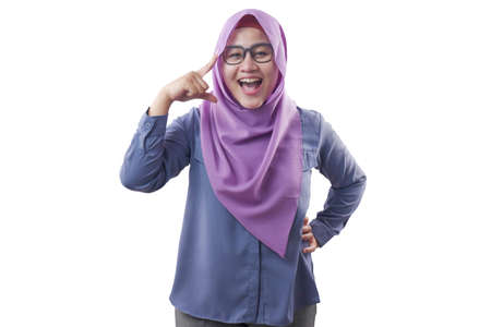 Portrait of smart beautiful Asian muslim woman smiling at camera and pointing on her head, idea intelligence and imagination concept Stock fotó