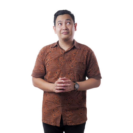Portrait of young Asian man wearing batik shirt looked happy thinking and looking up, having good idea. Half body portrait isolated on white Reklamní fotografie