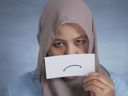 Portrait of Asian muslim woman with sullen card covering her mouth, pouting grim expression drawn on paper mask