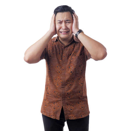 Young asian man wearing batik shirt covered his ear ignoring noise. Stressed under pressure concept isolated on white