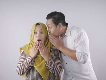 Man covering his mouth and whispering secret to his wife ear, Asian muslim woman looking shocked and excited, opening eyes and mouth widely with surprise, family concept