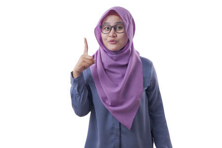 Young Asian muslim woman wearing hijab raising pointing finger, number one gesture, pick me concept, isolated on white