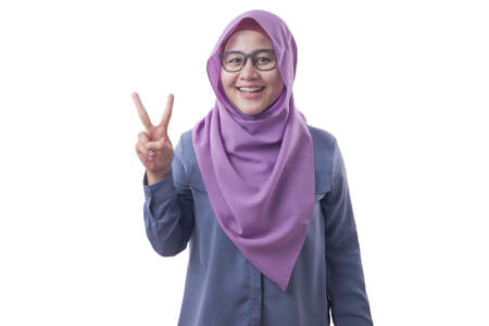 Portrait of muslim woman wearing hijab looking at camera, smiling and showing number two or peace sign gesture Stock Photo