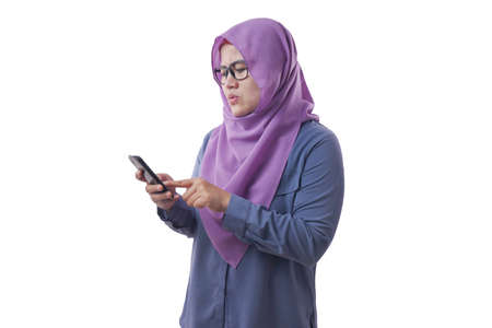 Young Asian muslim woman seriously looking reading massage on her phone. Close up body portrait. Isolated on white Stockfoto