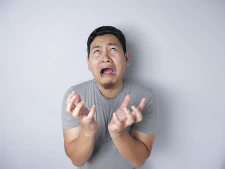 Portrait of funny Asian man crying hard, sad depression frustration hopeless expression