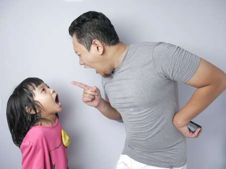 Young Asian father and little baby girl daughter arguing, screaming each other, dad mad at his kid Banque d'images - 131686692