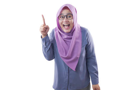 Portrait of happy Asian muslim woman having bright idea, looking at camera, smiling and pointing up, excited gesture, isolated on white