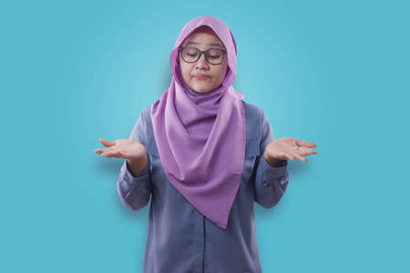Portrait of Asian muslim woman shows something on her empty open palms, thinking looking and making a choice beetwen hands gesture, empty copy space concept