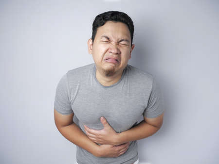 Portrait of young Asian man squezze his stomach for having stomachache pain, against grey wall