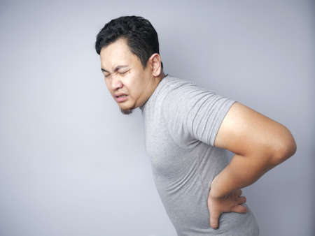 Young Asian man suffers from ower back pain. Close up body portrait over grey wall Stock fotó