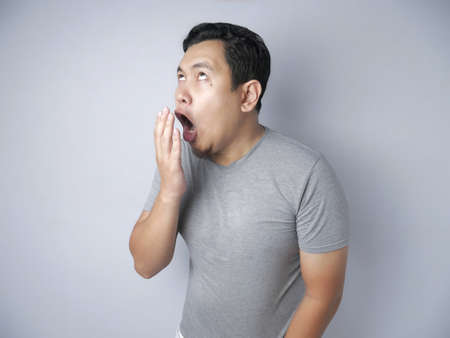 Portrait of funny Asian man check his own breath, mouth smell odor