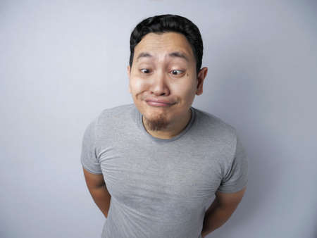 Portrait of funny Asian man looking at camera and smiling with silly expression