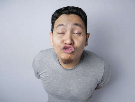 Portrait of funny silly Asian man trying to kiss, against grey background 写真素材