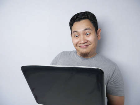 Young Asian man working typing on his laptop, smiling expression. Close up body portrait against grey background