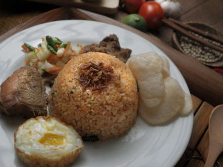 Food photography, Nasi goreng or Indonesian fried rice, served with fried egg and chicken curry