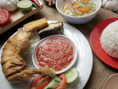 Food photography, Indonesian fried chicken or ayam goreng served with sambal and white rice Stock Photo