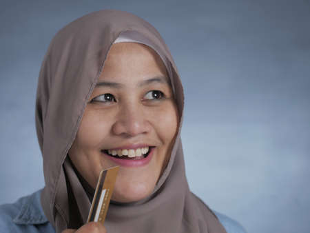 Portrait of Asian muslim woman smiling and thinking while holding credit card