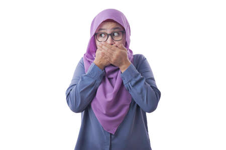 Close up portrait of Asian muslim woman wearing hijab closing her mouth with fingers. Worried gesture lookign to the side, can't say anything. Shocked surprised to hear bad news or gossip