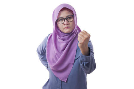 Portrait of Asian muslim woman pointing at camera with angry expression, giving warn, isolated on white