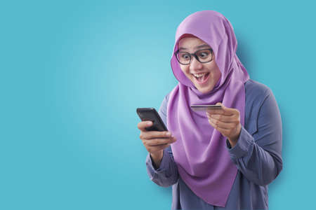 Portrait of Asian muslim woman smiling and making purchase buying online from her mobile phone, e-commerce concept