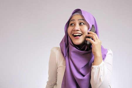 Portrait of muslim lady wearing hijab talking on phone, happy smiling expression having good news Stock fotó