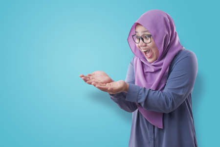 Portrait of Asian muslim woman wearing hijab shows copy space empty palm presenting something, excited smiling expression over blue background