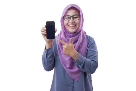 Portrait of Asian muslim woman looking at camera smiling, showing and pointing her smart phone, phone mock up, isolated on white 免版税图像