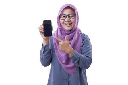 Ritratto di donna musulmana asiatica che guarda la telecamera sorridendo, mostrando e puntando il suo smartphone, telefono mock up, isolato su bianco Archivio Fotografico