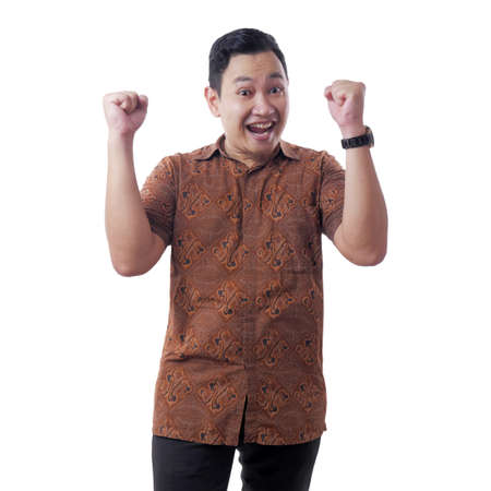 Portrait of successful young Asian man wearing batik shirt shows winning gesture, celebrating victory. Hands raised above, isolated on white