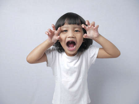 Portrait of funny little Asian girl with bad tooth doing tiger roar gesture