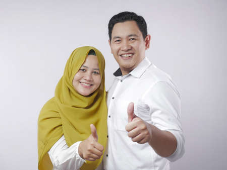 Portait of happy Asian muslim couple smiling and shows thumbs up gesture, husband and wife hugging full of love, family concept Archivio Fotografico