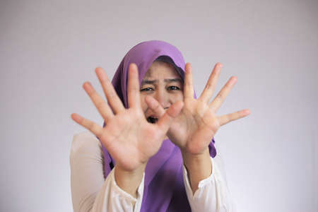 Portrait of sad Asian muslim woman having bad experience making stop hand sign gesture, bullied concept Stock Photo