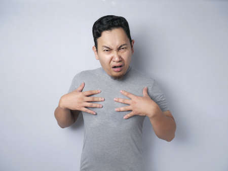 Asian man pointing himself with unhappy displeased expression as if he confused to be accused and asking who? me?