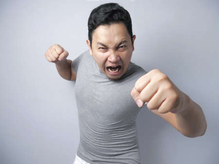Photo image of funny Asian man showing cynical unhappy angry facial expression putting up his fist challenge to fight