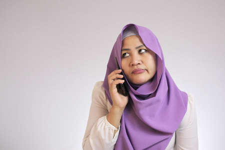 Portrait of Asian muslim woman looks annoyed, too long waiting on the phone Imagens