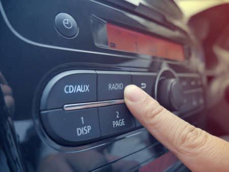 Close up image of drivers hand press button on car radio, listening music during trip concept