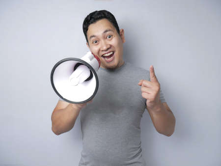 Young Asian man making announcement, advertisement concept, Smiling expression using megaphone. Close up body portrait over grey background