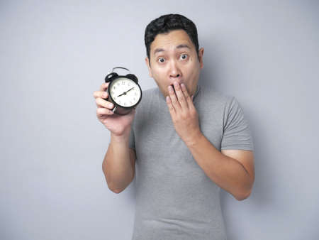 Portrat of funny young Asian an wearing grey shirt worried by time when looking at a clock. Close up body portrait