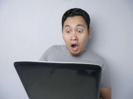 Portrait of funny Asian man shocked with big eyes and open mouth when looking at his laptop, against grey background